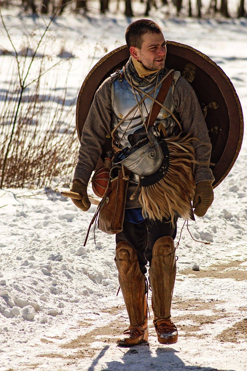 man wearing armor and walking in snowy field