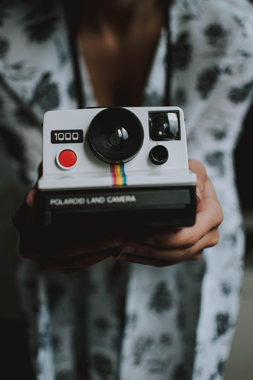 person holding white polaroid land camera