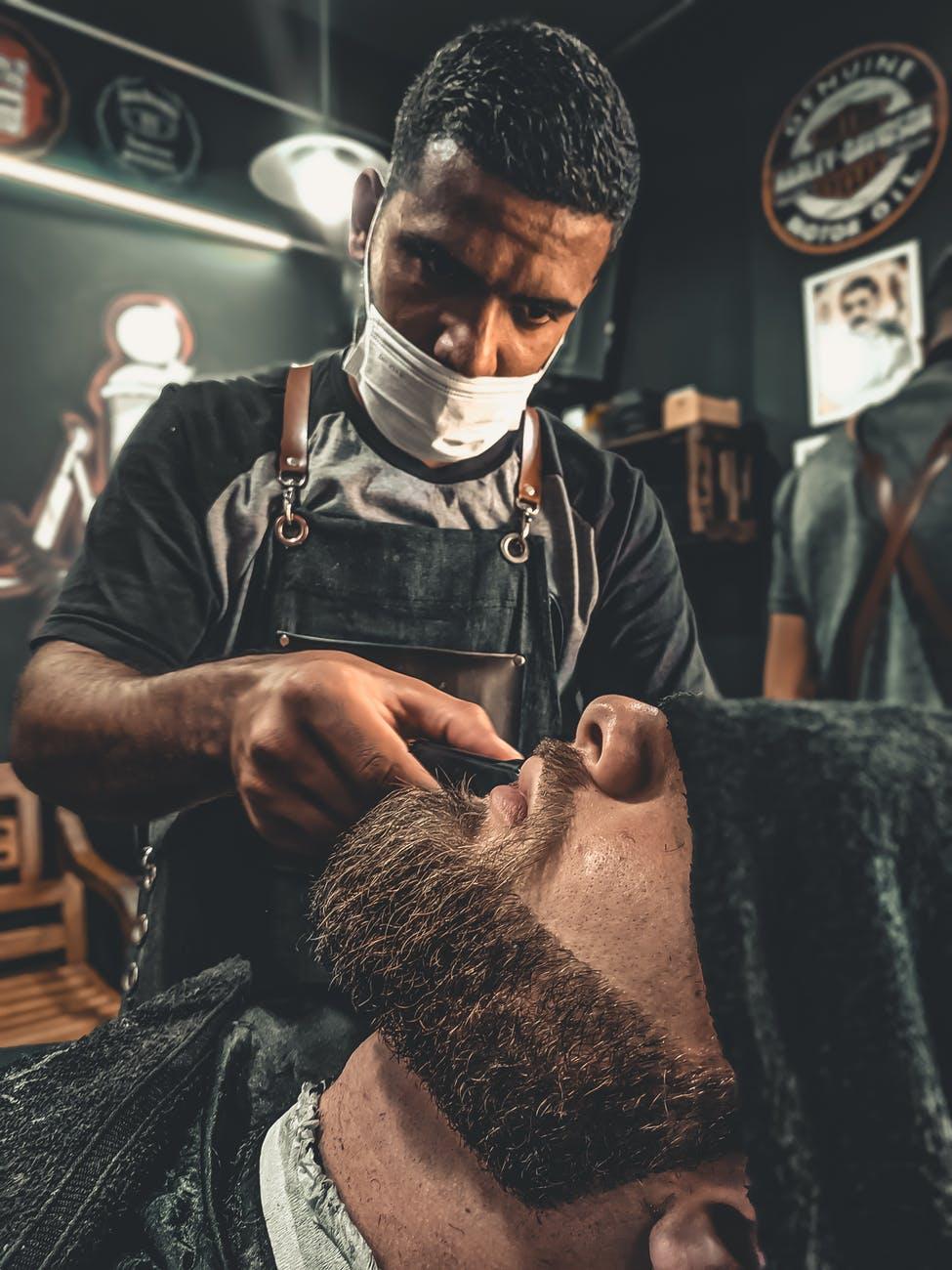 a barber grooming a man s beard