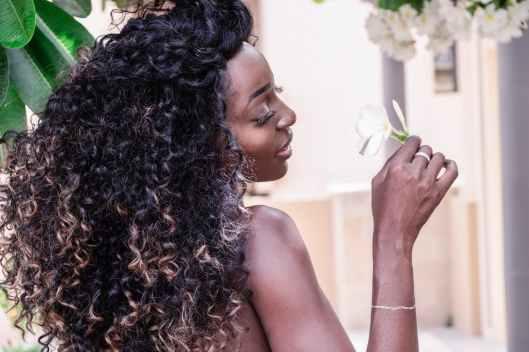 woman holding white plumeria flower