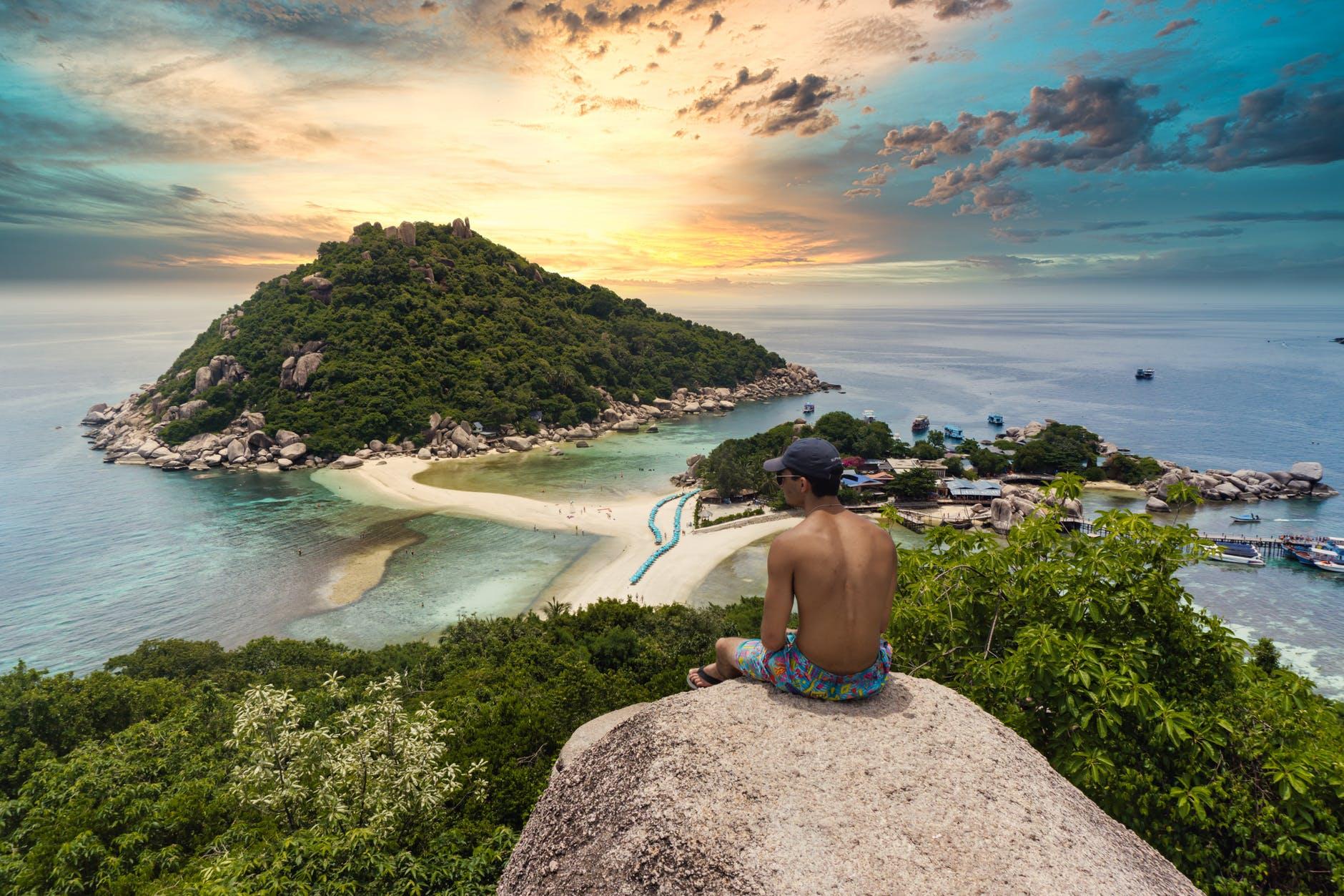 shirtless man sitting on a rock