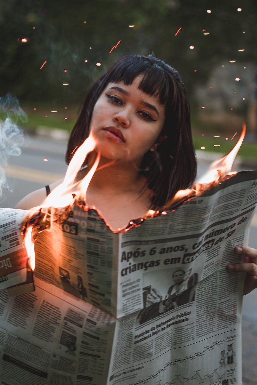 woman holding burning newspaper