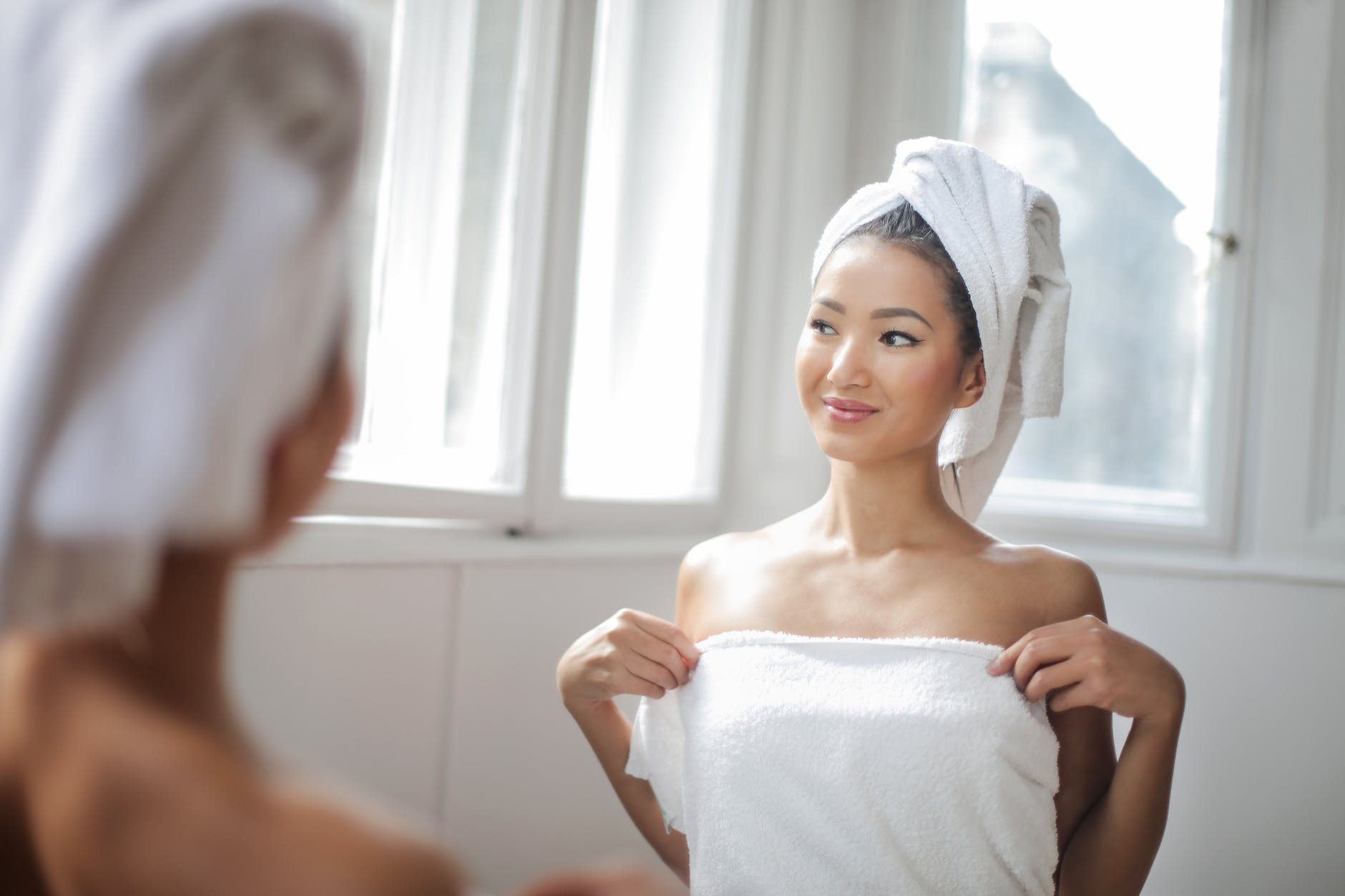 woman in white towel standing in front of the mirror