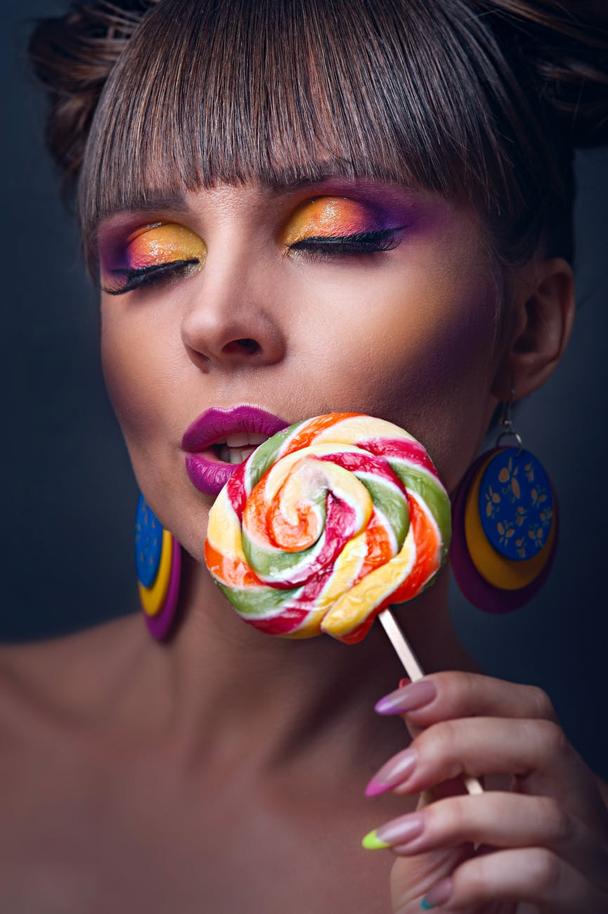 close up photo of woman holding lollipop