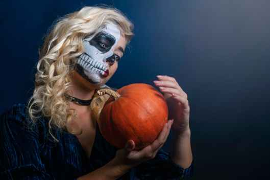 woman with face paint with pumpkin