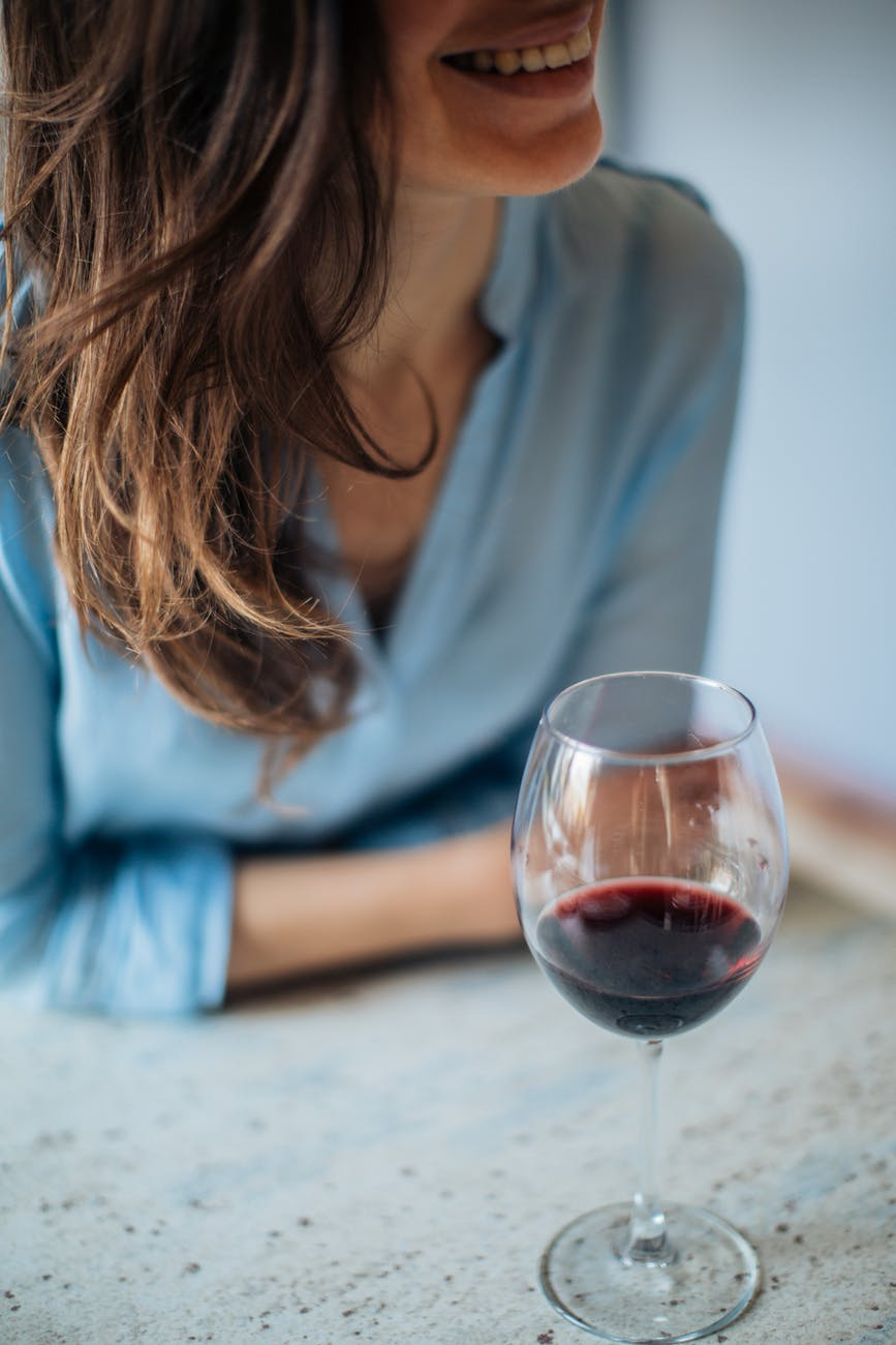 photo of woman near wine glass
