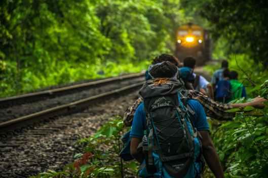 group of people walking beside train rail