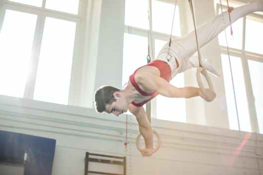 photo of male gymnast practicing on gymnastic rings